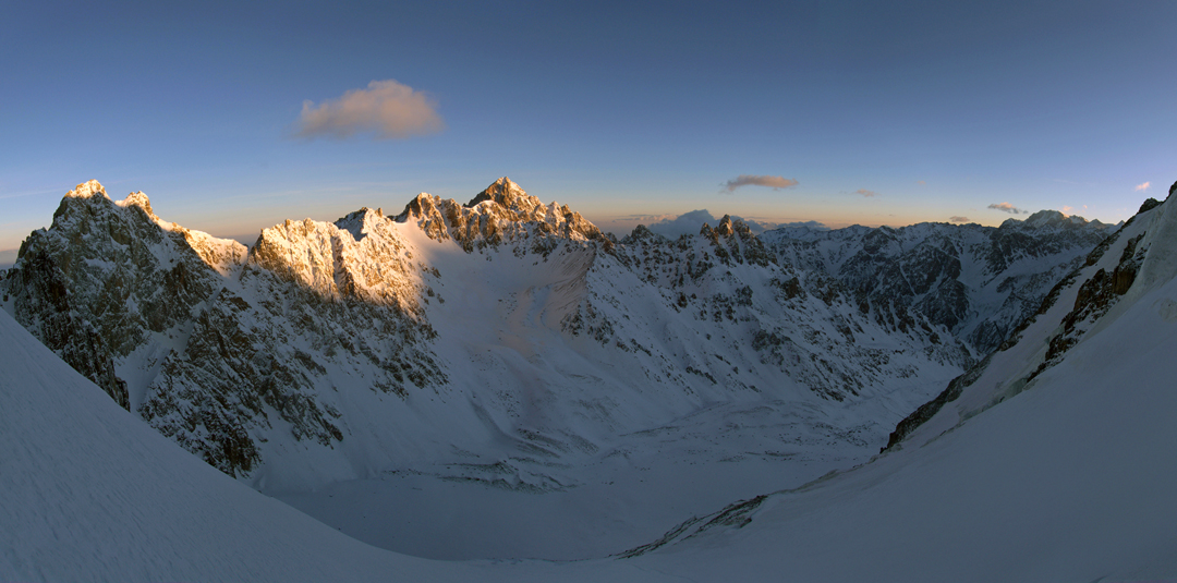 The view north to east from Pik Ordzhonikidze at sunrise. The high pyramid in the sun left of center is Pik Komsomola (4,248m). On the very far right, the broad-topped high mountain is Pik Talgar (4,973m), the highest summit of the Zayliyskiy Alatau.
