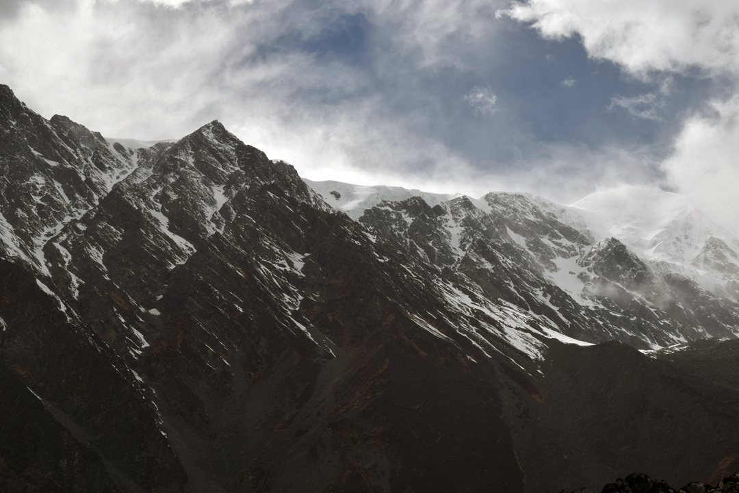 The northeast face of Nyambo Konka (6,114m). JJ Cieslewicz and Mark Jenkins climbed the dogleg couloir on the left side of the image to reach the crest of the south-southeast ridge, which they followed up right to the domed summit, just visible in cloud.