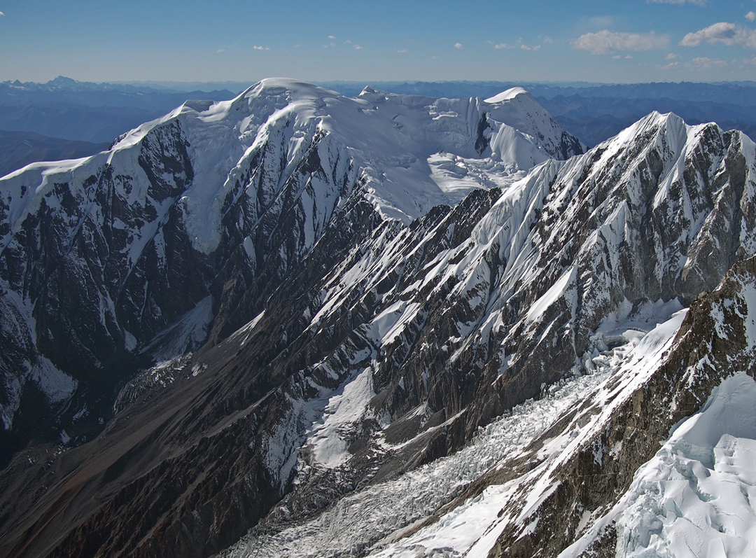 Nyambo Konka (6,114m) from the east-northeast. The Korean first ascent (2015) and several previous attempts slanted up the rocky face from the left to reach the east-northeast ridge (dropping almost toward the camera from the dome-shaped summit) at the low point (5,596m) between Nyambo Konka and the near peak on the far right. The Koreans then followed the snowy east-northeast ridge away from the camera to the summit. The upper south-southeast ridge, climbed in 2017, forms the left skyline, the crest reached via a couloir on the northeast face off picture to the left.
