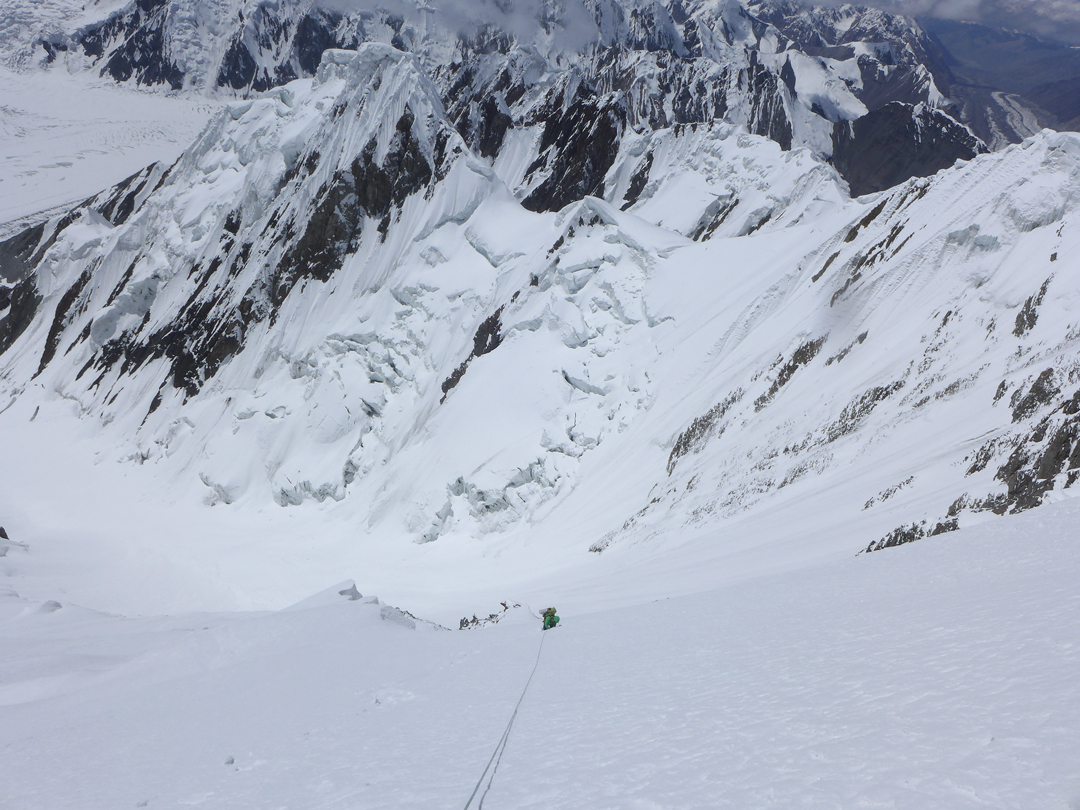 Descending the steep snow face below the col between Ak-tau and Pik Pyramida. The narrow glacier below was followed down to the Zvezdochka Glacier, part of which is visible top left, to return to base camp.