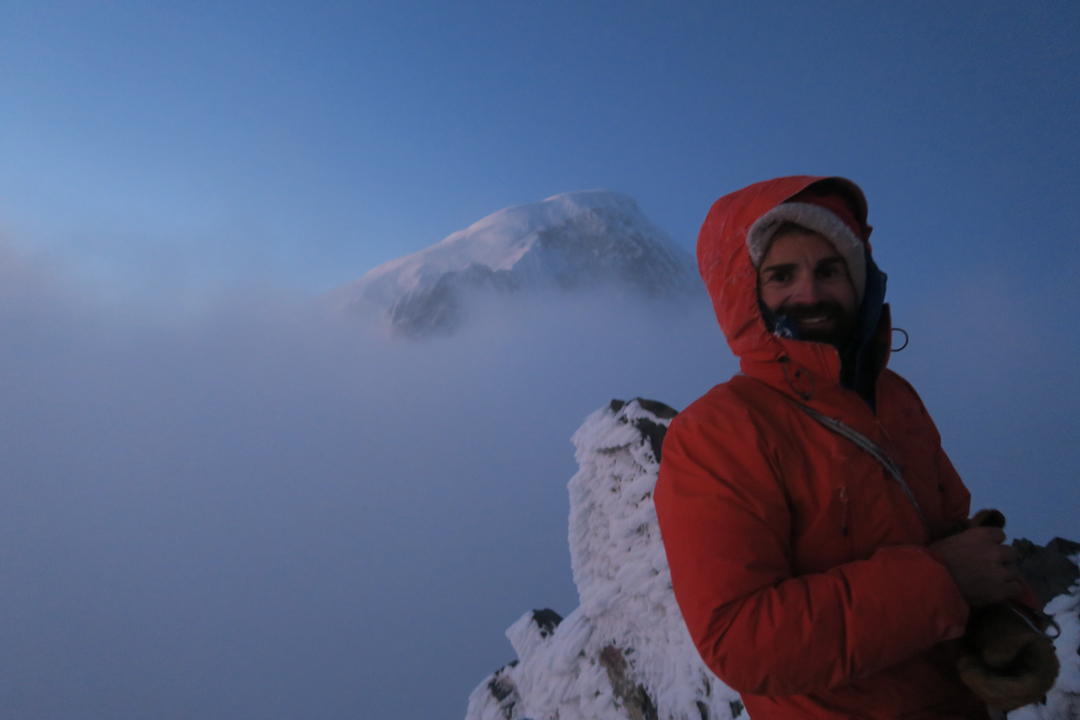 "Francois Poncet on the summit of Pilar Sur with the summit of Cerro San Lorenzo in the background. Jerome Sullivan writes, ""You can read the madness in Ponpon's eyes."""