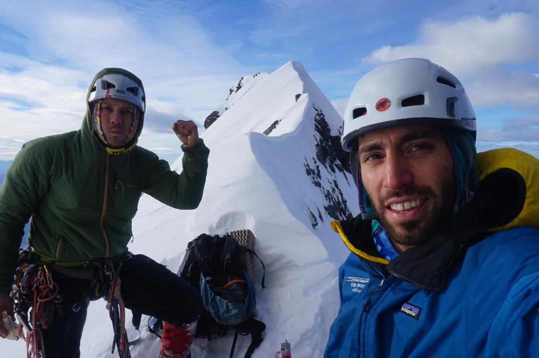 Felipe Bishara and Christian Barra Muñoz at a brief rest near middle-height on the south face of Cerro Almirante Nieto, before climbing the upper southeast face.
