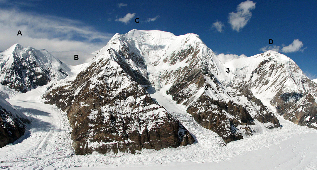 The south face of Bayancol, seen across the North Inylchek Glacier from Khan Tengri. (A) Pik Odinadtzaty (5,437m). (B) Odinadtzaty Pass (4,850m). (C) Bayancol (5,841m). (D) Pik Kazakhstan (5,761m). (1) The obvious southwest ridge leading directly to the summit does not appear to have had any ascents. (2) Southwest spur to southeast ridge (2018, 5A). (3) Southeast ridge (5A, 2008).