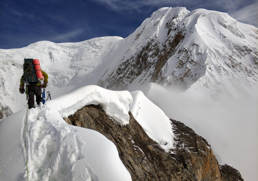 Tursunali Aubakirov atop a gendarme on the southwest spur leading to the southeast ridge of Bayancol. The southwest spur reaches the southeast ridge at the snowy shoulder in upper right, and the summit is visible in the background, almost in the center of the picture.