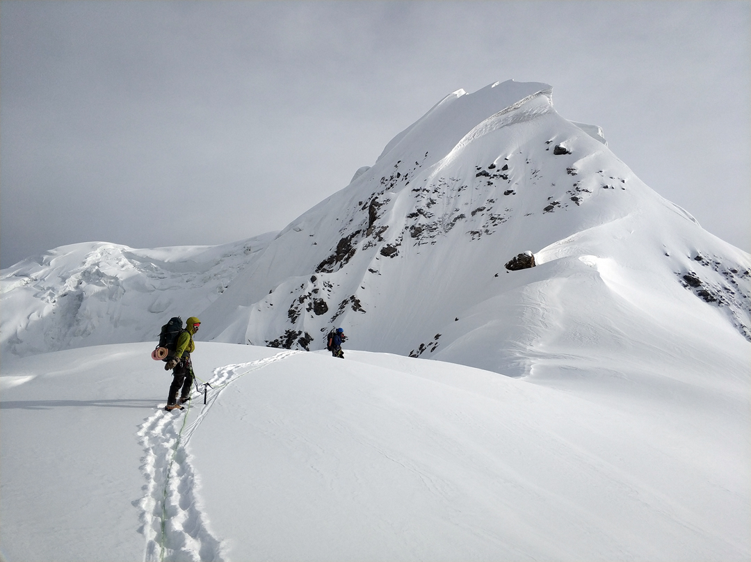 Tursunali Aubakirov following Igor Malkin on the upper section of the southeast ridge of Bayancol, with the top section of the unclimbed southwest ridge forming the left skyline.