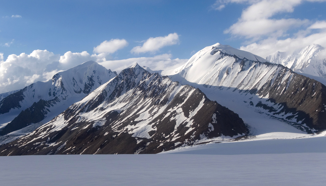 Peak 5,560m, in the center foreground, was summited by Belotserkovskiy and Ten via the west ridge, rising from the left. To the right is Dom Brakk (5,830m), with the usual route of ascent following the obvious glacier bay to the col right of 5,560m, and then up the snow ridge and snow slopes to the summit.