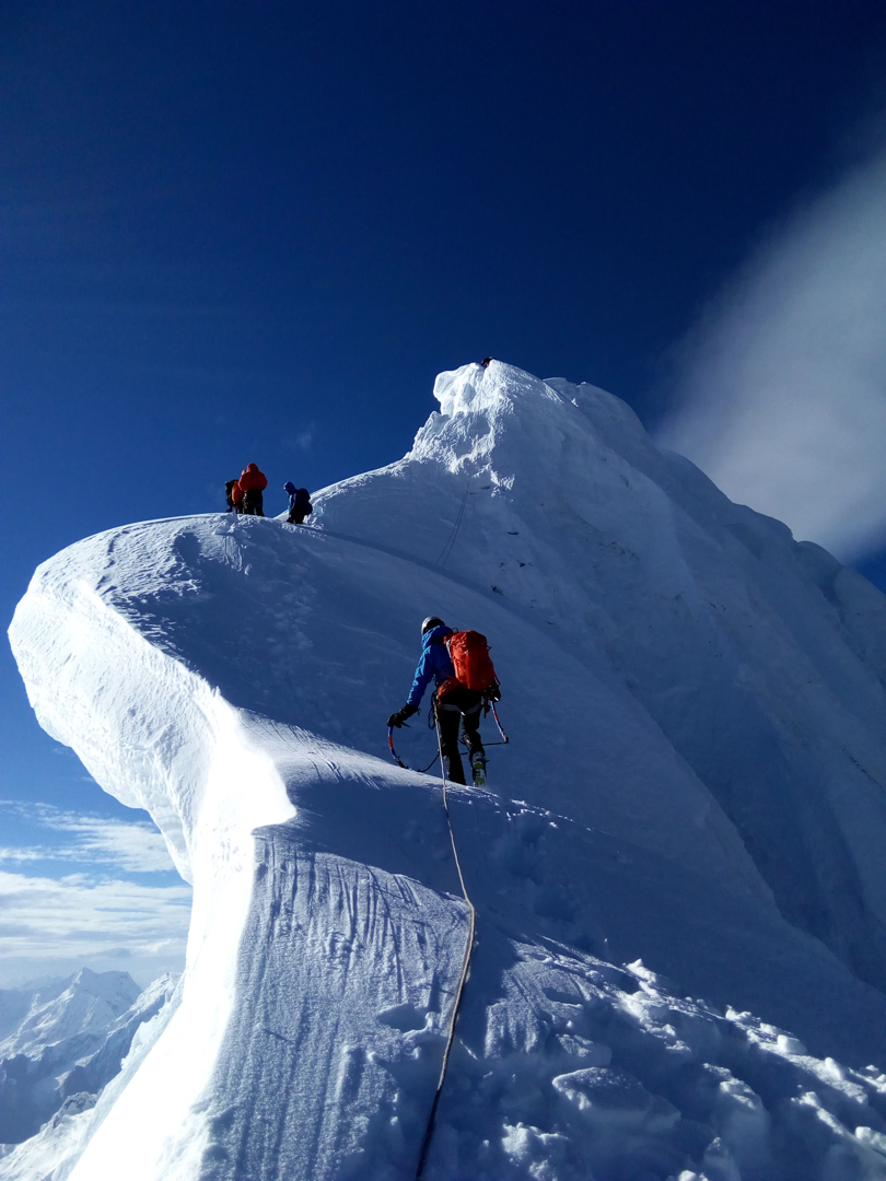 The team approaches the overhanging summit cornices of Nevado Huantsán.