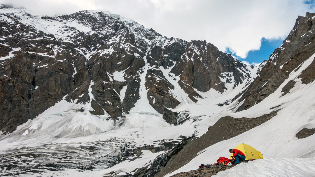 Ruud Rotte at the bivouac below Ghaintar Chhish. The southeast ridge is the right skyline. The central snow couloir is threatened by a serac. The rock is terrible.