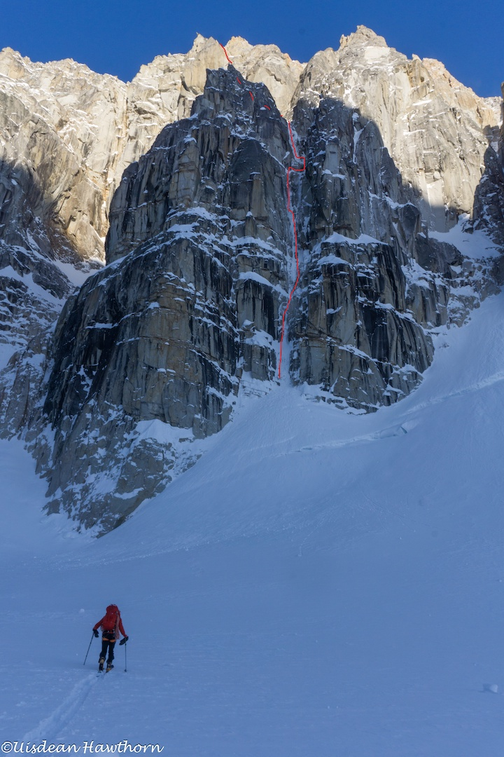 Tom Livingstone approaching the east face of Jezebel in Alaska's Revelation Mountains. The lower portion of Fun or Fear (1,200m, M6+ AI6 R 90˚) follows the obvious ice couloir.