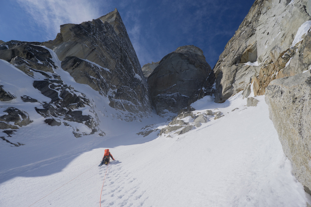 Uisdean Hawthorn exiting the narrow mixed couloir that defines the lower portion of Fun or Fear (1,200m, M6+ AI6 R 90˚) on the east face of Jezebel in the Revelation Mountains. From the top of this broad gully, Hawthorn and Tom Livingstone headed up the narrow cleft on the left.