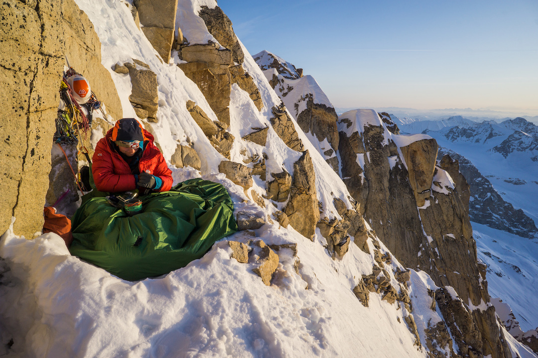 Uisdean Hawthron soaking up the morning sun during the first ascent of Fun or Fear (1,200m, M6+ AI6 R 90˚) on the east face of Jezebel in the Revelation Mountains.