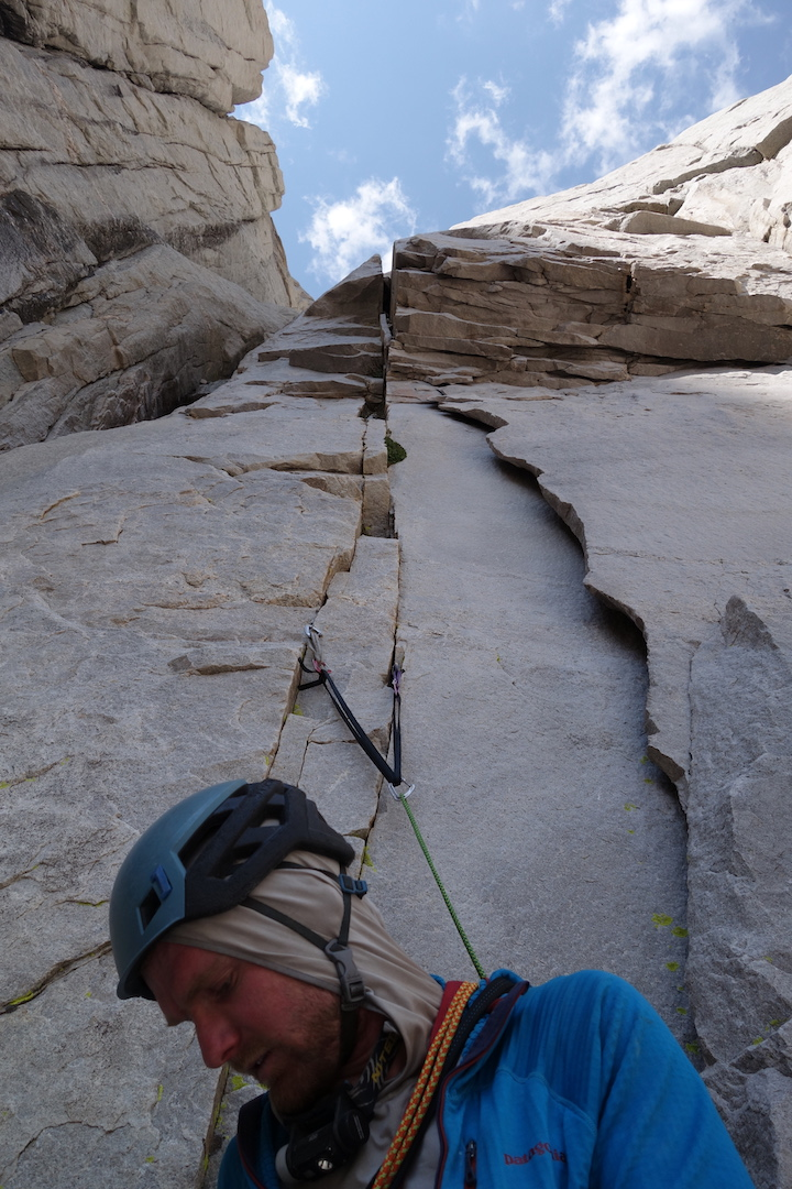 Patrick Longley below the fourth-pitch wide crack of Until the Wheels Fall Off (1,100', IV 5.11 C1) on the west buttress of Mt. Chamberlin's northeast face.