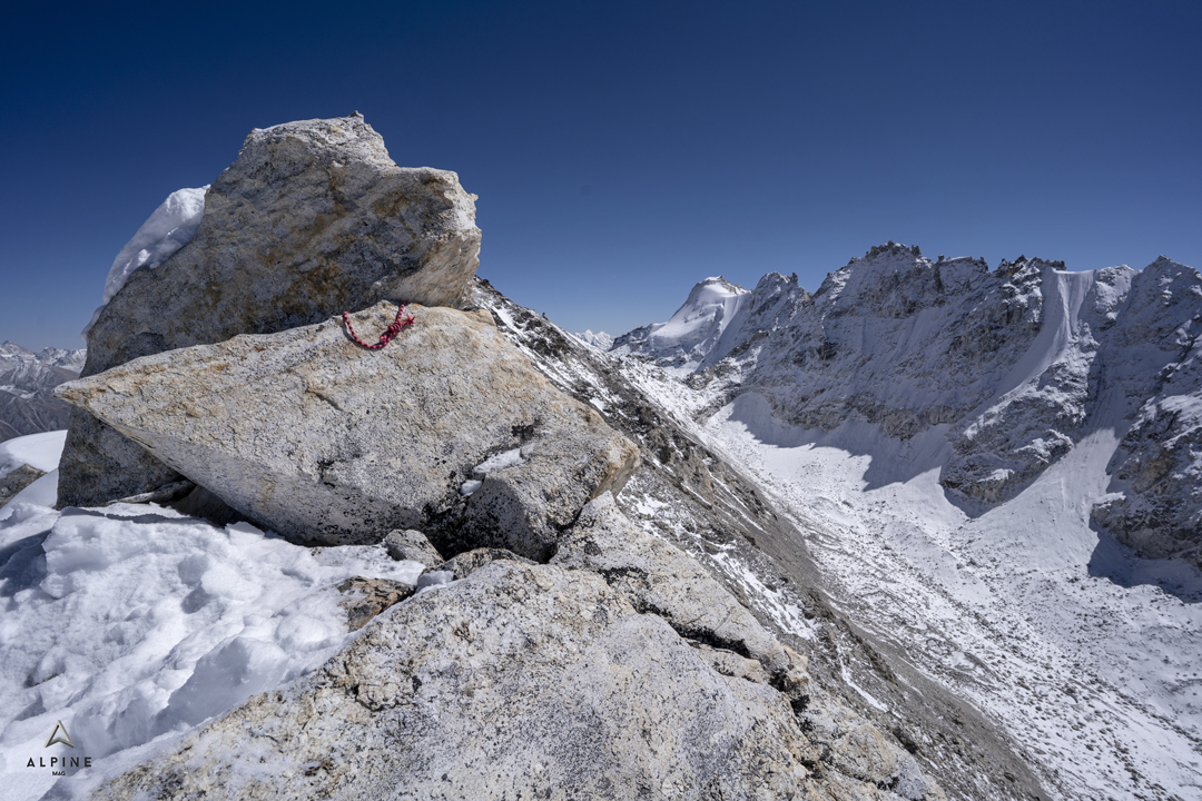 The summit of Steph Himal, looking southeast up the valley to the south, with the far distant snowy summit (through the gap) of Peak 6,084m (unofficially known as Sumdo Himal). The rope sling was left by the French first ascensionists as a discreet legacy of their visit.