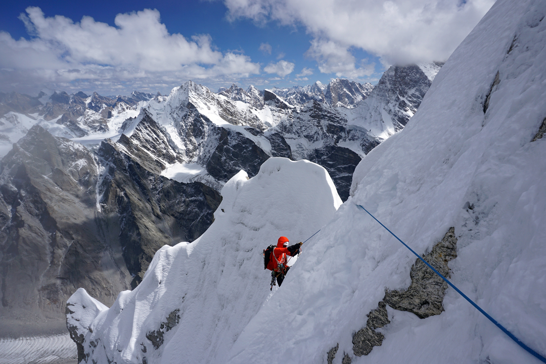 Yusuke Kato below the headwall of Cerro Kishtwar northeast face. The high peak background right is Kishtwar Kailash (6,451m, summit in cloud), first climbed in 2013 by Mick Fowler and Paul Ramsden.