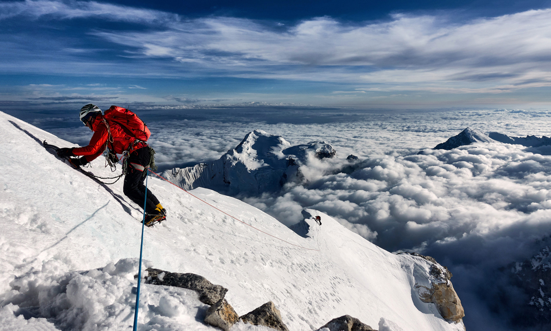 Paul Figg (foreground) and Malcolm Bass start their descent of the south-southwest ridge of Janhukot in the afternoon sun. Mandani Parvat (6,193m) rises out of the cloud behind.