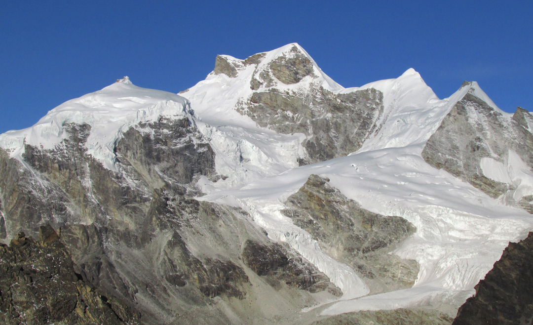 Churau (6,419m) from the southeast. The route of ascent crossed glacier slopes to reach the east ridge (right skyline) then the triangular snowy subsummit to the main top.