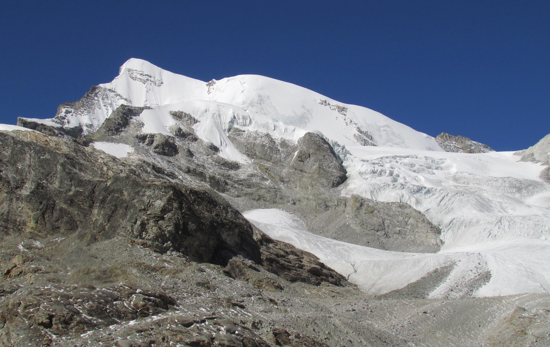 Peak 6,265m from the southeast. The route of ascent climbed the snow slopes facing the camera, immediately left of the rock outcrops, and then continued up the northeast ridge to the summit.