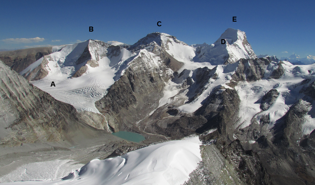 Looking southeast from Peak 6,265m at the Koji La lake and (A) Koji La (5,495m on the map, but now around 5,470m), (B) Koji Kang North (6,275m, climbed in 1997 by a Japanese team via left-hand ridge), (C) a peak of ca 6,600m entirely in Tibet, (D) Myung Thang Kang (6,449m), and (E) Kaqur Kangri (6,859m). In the far right background is Dhaulagiri.