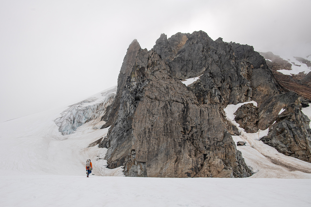 Forest McBrian approaches the toe of the buttress at around 7,600' on the Quien Sabe Glacier, west of the summit of Sahale Mountain. The climbing route ascended the series of towers on the climber's left side of the massive spur.
