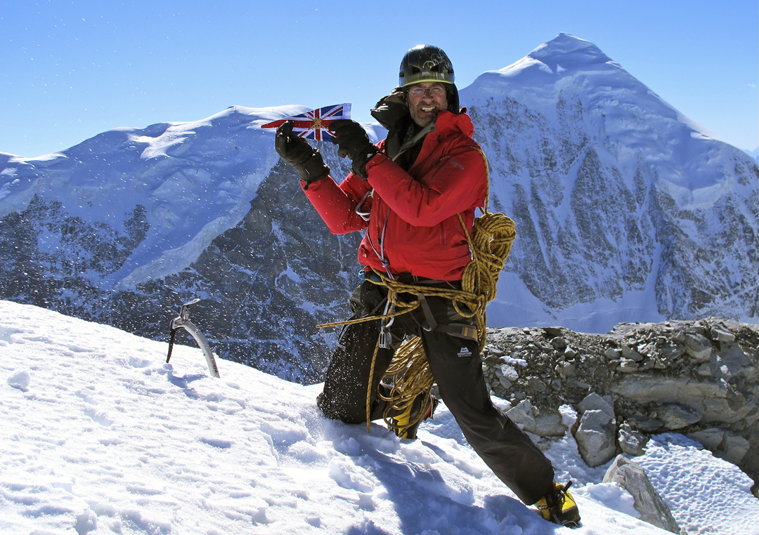 Duncan Francis on the summit of Wupingfeng in December 2012 with the impressive north-northwest face of Lamo-she in the background. The upper section of the northeast ridge, which descends left from the summit, was followed by Tomas Franchini on his solo ascent from the opposite side. The only previous known ascent of Lamo-she took place in 1993, when it was climbed by Americans who came up the glacier below the northwest face, then followed the steep west-northwest ridge (right skyline in this photo).