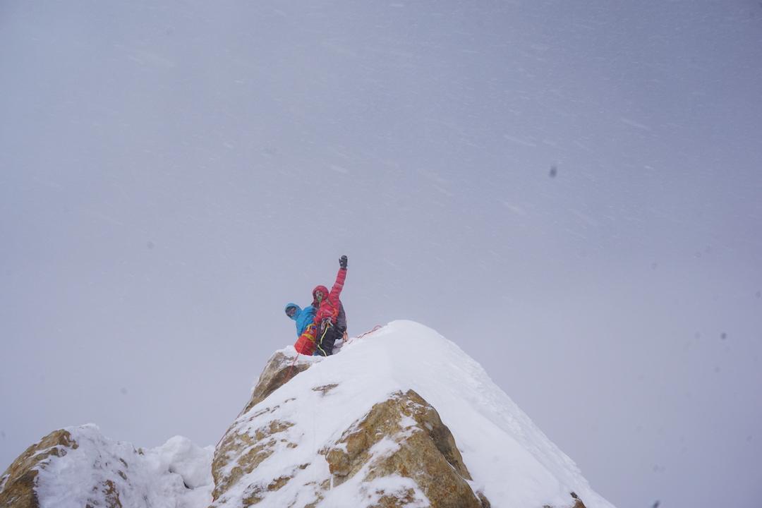 Alex Česen and Luka Stražar reaching the summit of Latok I in blowing snow.