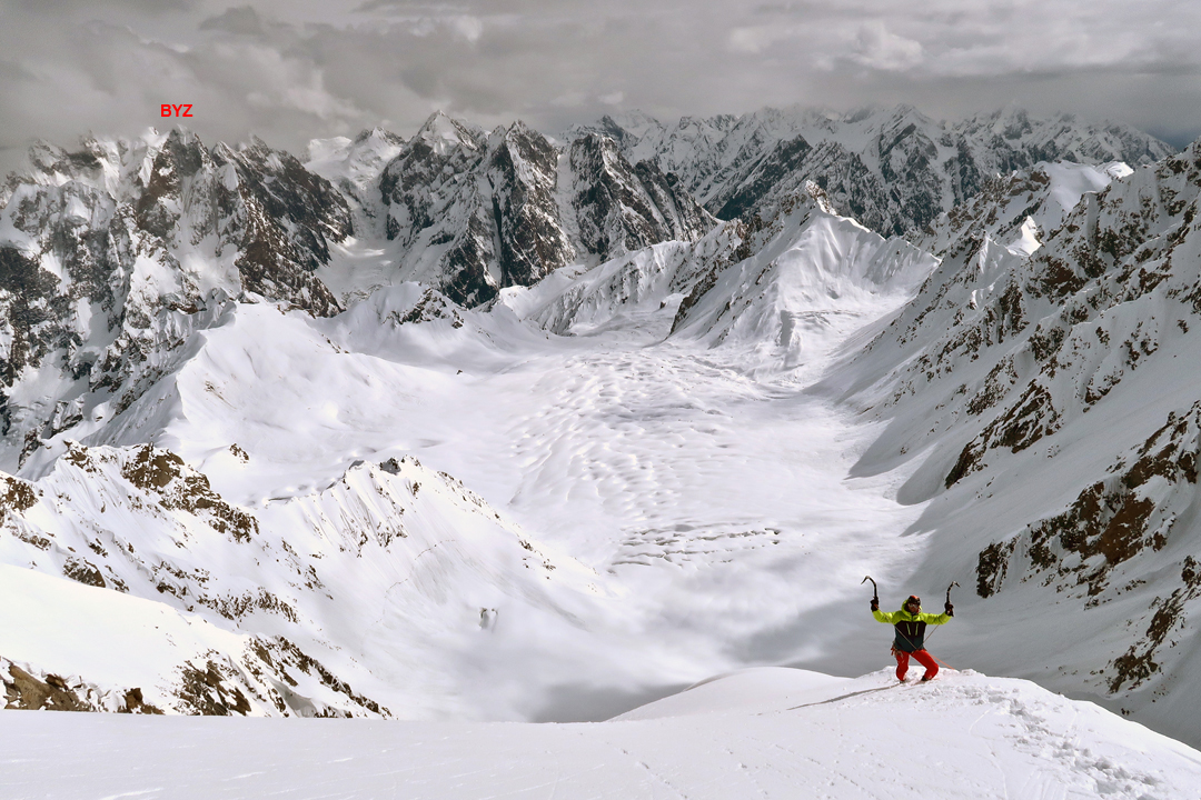 Aurélien Vaissière on the summit (southwest) ridge of Risht Peak. The view is south down the Zhang Tek Glacier with little-known peaks of the Gazen Group. The high peak marked in background left is Blatts Yaz Zom (6,191m).