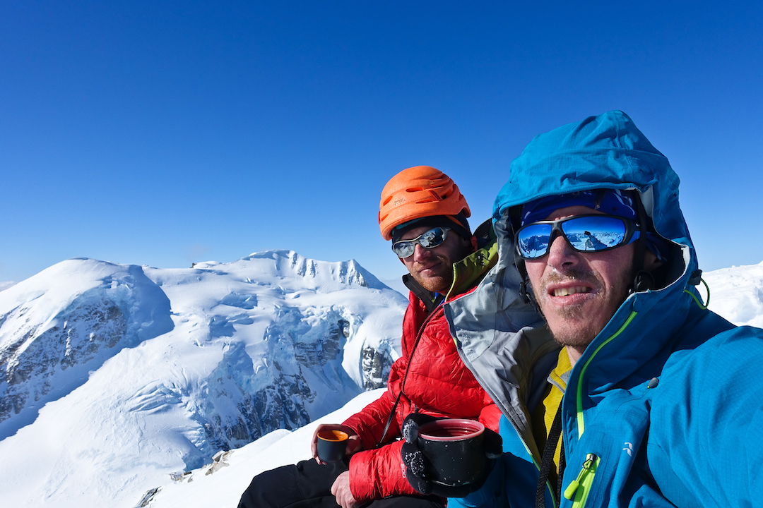 "Bas Visscher and Niek de Jonge on the summit of ""Tantalus"" (Peak 8,910') after making the first ascent of the south couloir. The summit ridge of Mt. Titanic is behind them."