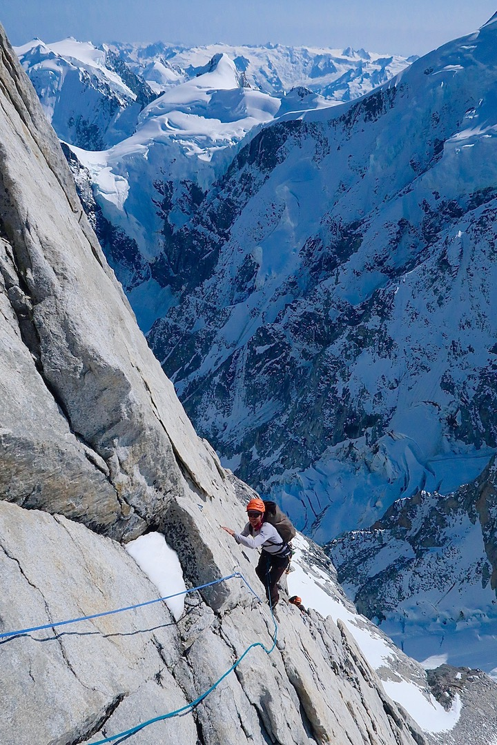 Tony Richardson following the fifth pitch of Peaceful Warrior (750m, TD- 5.11a) on the rightmost buttress of Mt. Combatant's southwest face. The lower northeast face of Mt. Waddington is visible behind.