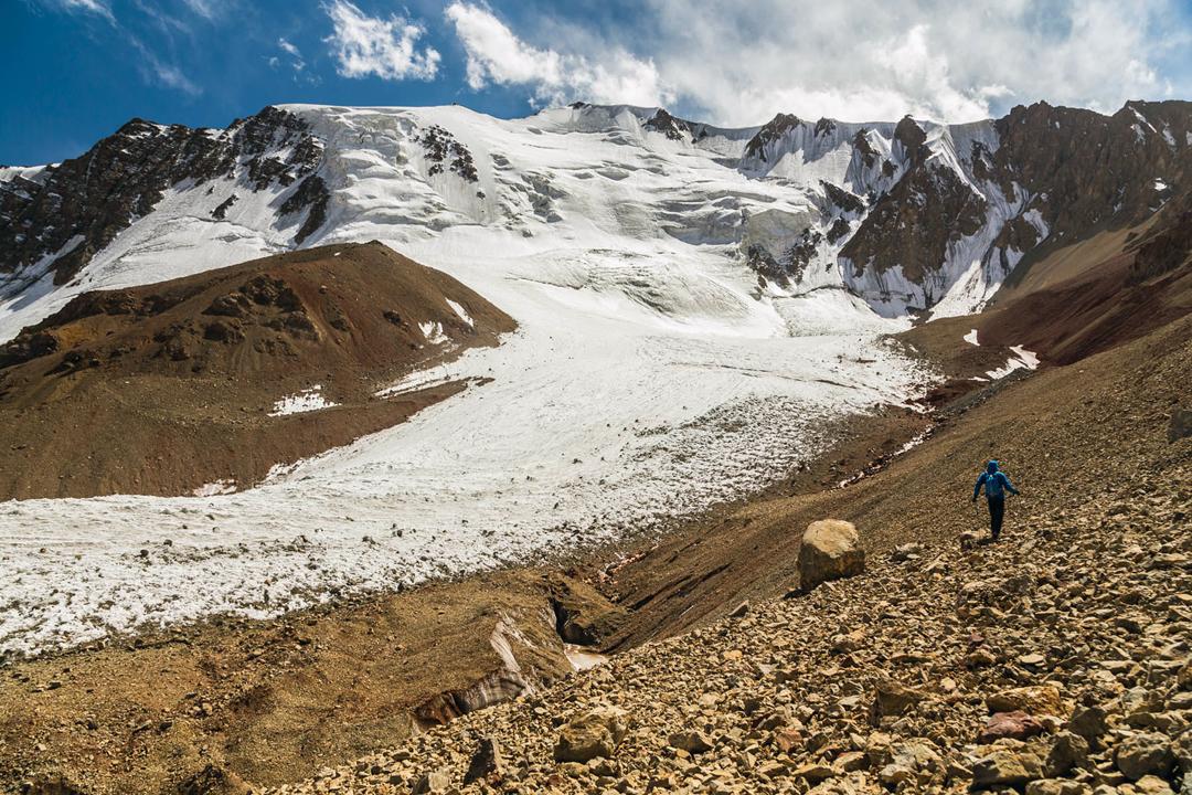 Jerzy Kędra heads along glacier moraine toward the north face of Pik Agamau.