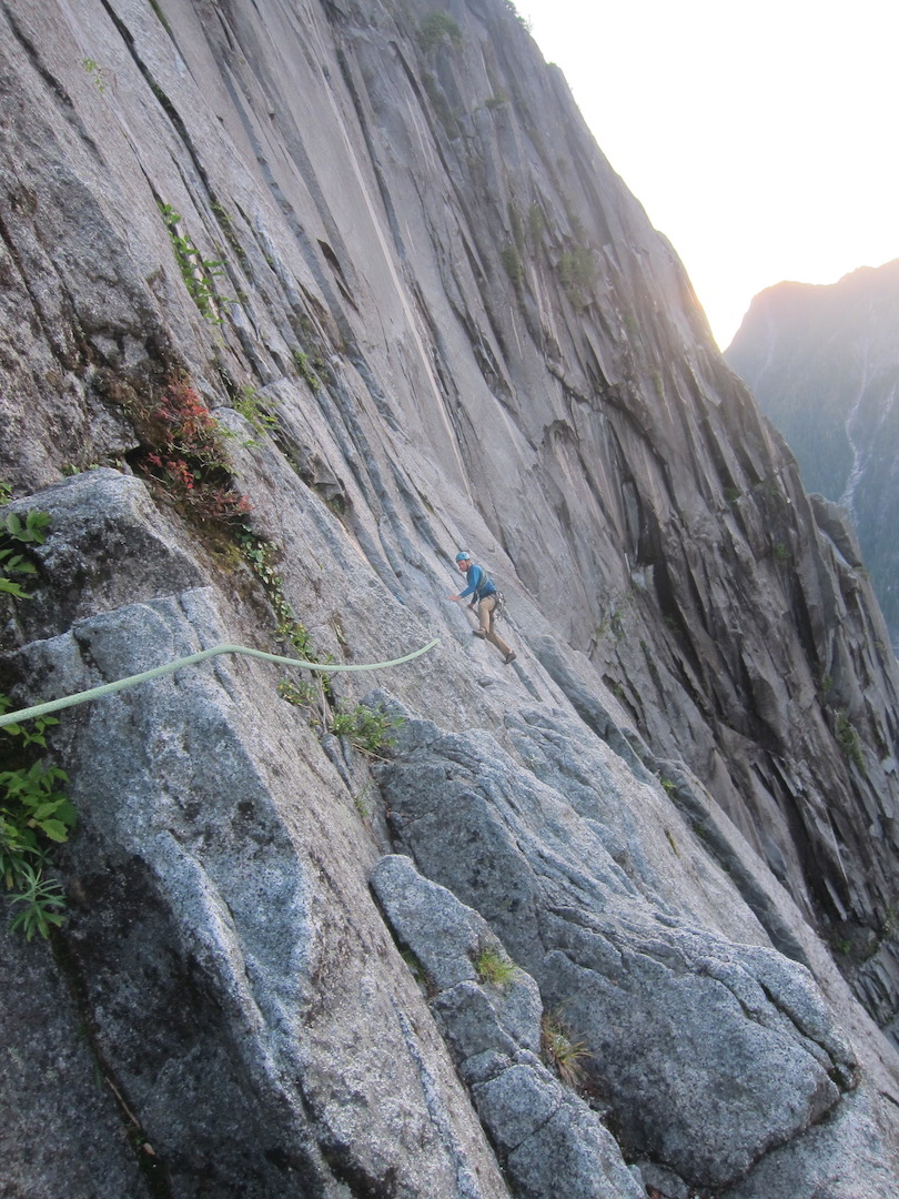 Josh Schuh seconds pitch 14 of Schneider Quits (1,200m, 27 pitches, 5.10+ A2+), a 5.9+ face traverse, as the evening light begins to fade at the end of his and Colin Landeck's second day on the Super Unknown in the Daniels River Valley.