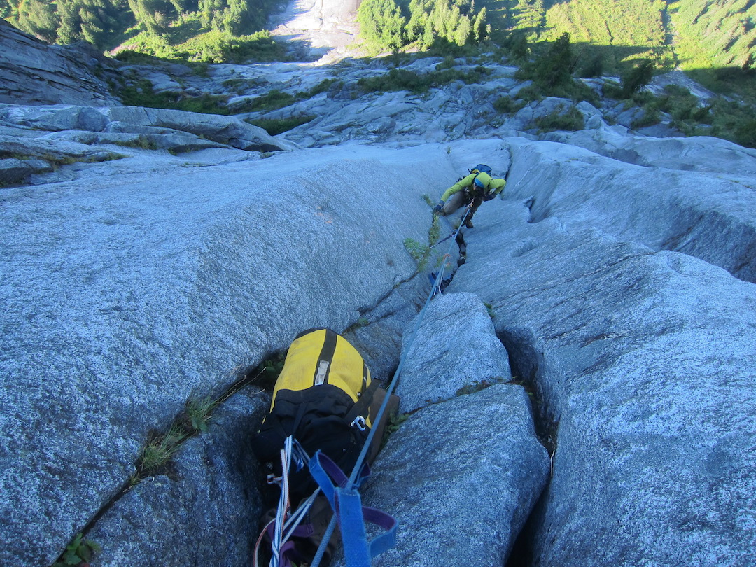 Josh Schuh cleans pitch 17 of Schneider Quits (1,200m, 27 pitches, 5.10+ A2+) on the Super Unknown, one of the four main granite walls in the Daniels River Valley. They established the fourth complete line on the formation over five days in August 2019. This and nearby pitches held the most difficult and exciting free climbing of their route, epitomized by clean white granite, forming just off-vertical corners and splitters.