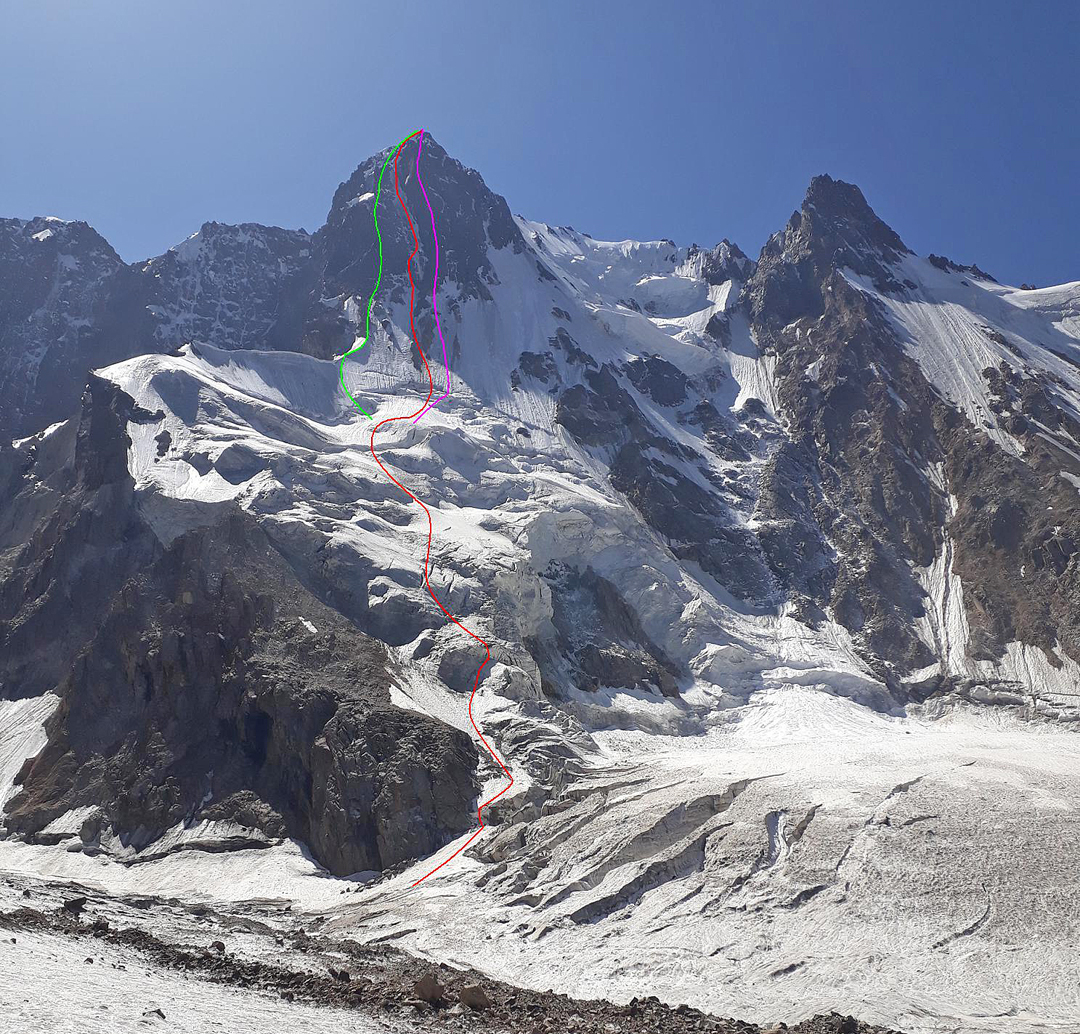 The northeast face of Sauk Dzhaylyau Central. (Green) Moskaltsov Route (pre-1984). (Red) Kashevnik-Tyulyupo Route (2019). (Violet) Kovtun Route (1978). The summit on the right is Sauk Dzhaylyau West II.