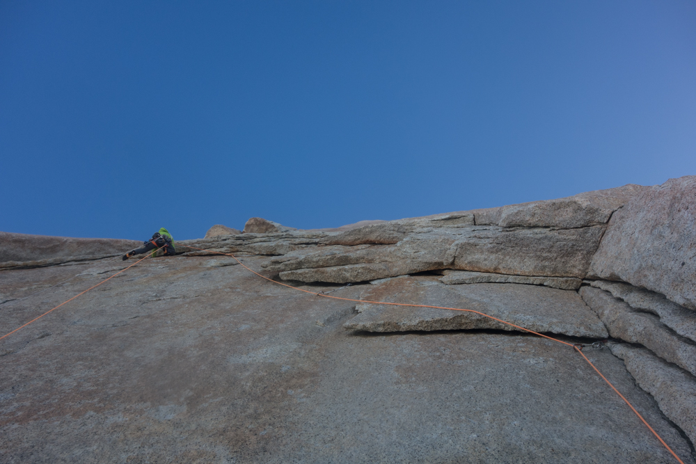 Nico Favresse traversing across a wild flake system on the southwest face of Aguja Poincenot.