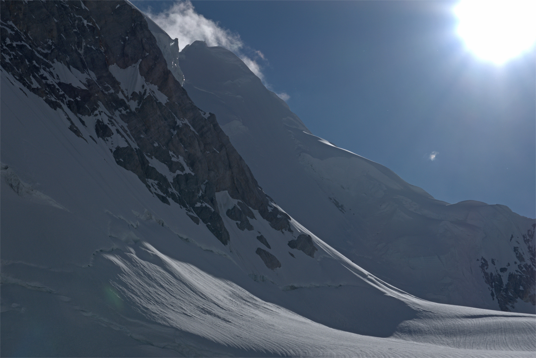 Seen from the upper southwest arm of the Gasherbrum Glacier, the northeast face of Gasherbrum VII lies in shadow. The first-ascent route climbed the steep snow slope, traversed over the top of the left-hand serac barrier, and crossed the upper bergschrund on the left, before continuing to the summit.