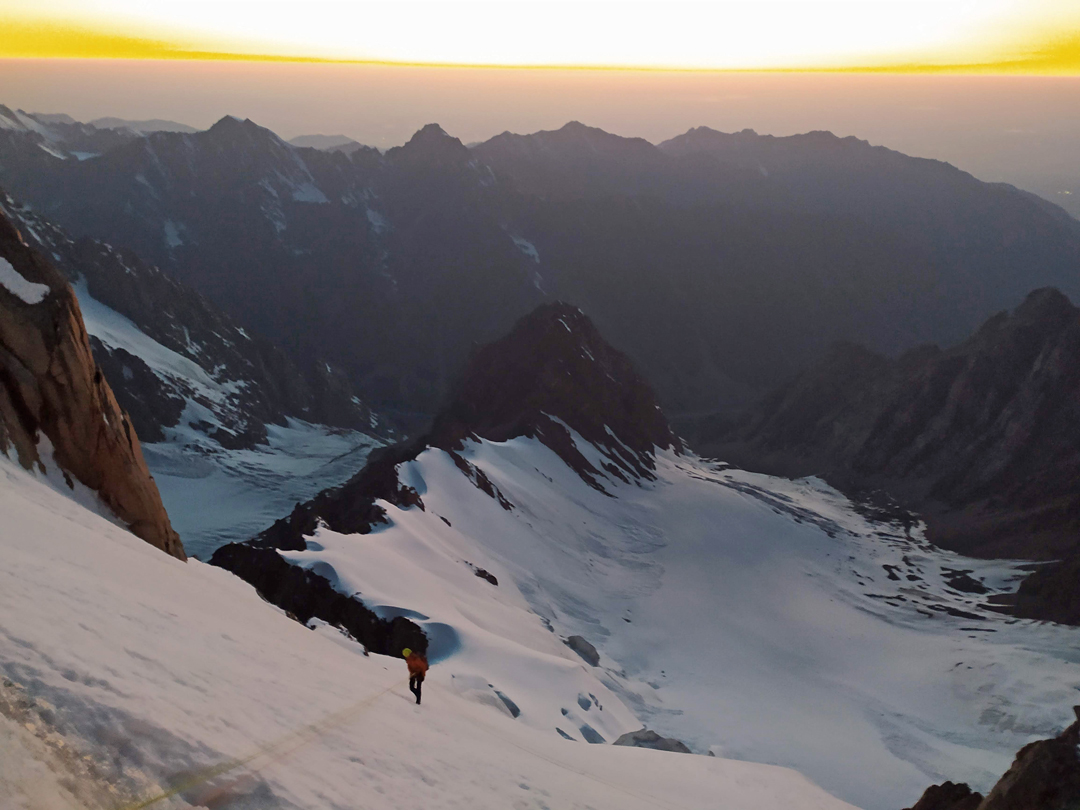 Kirill Belotserkovskiy heading down the descent route from Pik Trud in the last moments of daylight, rappelling northwest to gain the ridge connecting Trud to Pik Extra (4,012m).
