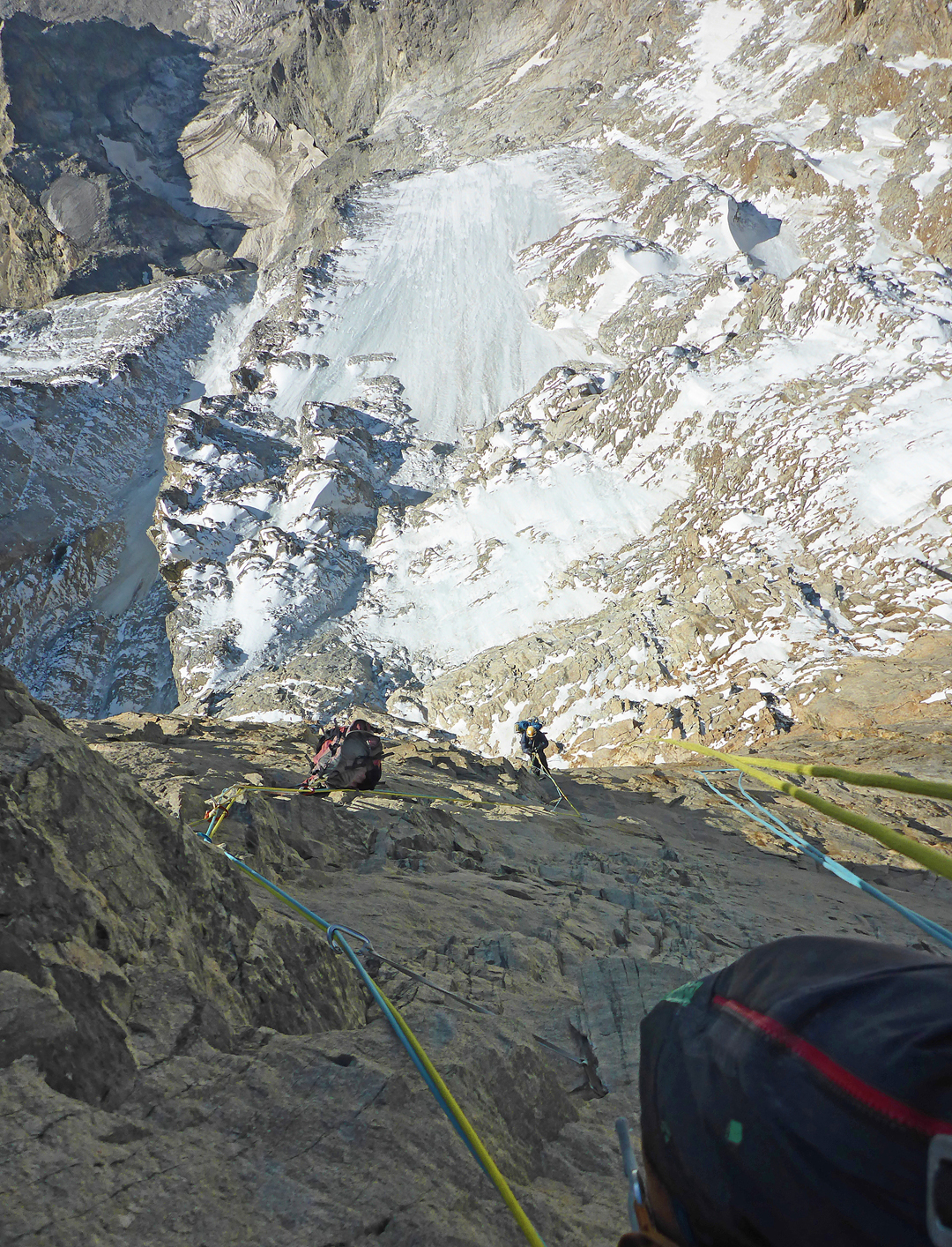 Giorgi Tepnadze follows a pitch on the Rockband. The middle icefield of the route is visible below.