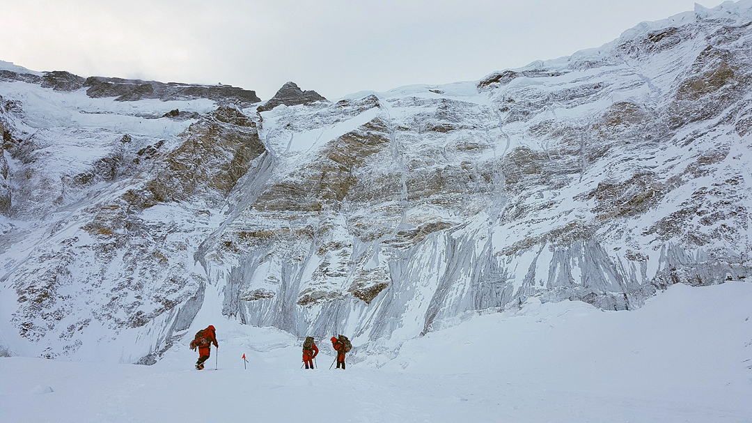 Approaching the lower north face of Pik Communism. The 2020 route of ascent climbed the 1,000m curving gray ice line above the right-hand climber.