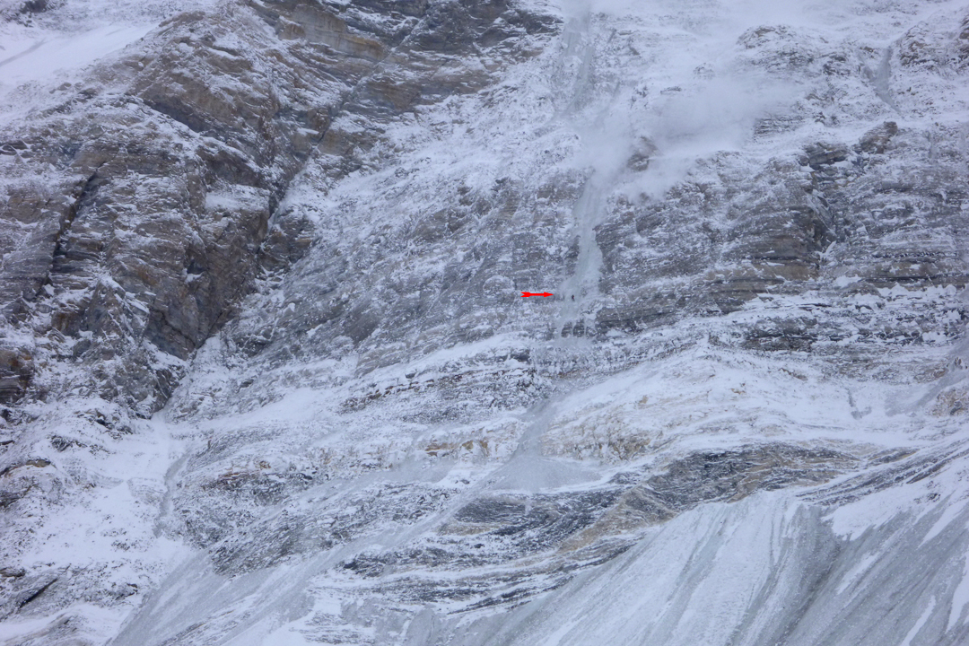 A climber (circled) at work on the middle section of the lower north face of Pik Communism during the first ascent of Barca.