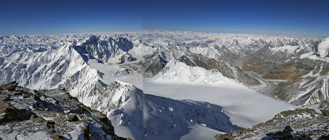 A panorama from the summit of Pik Communism looking from southwest (left) to north. The flat-topped peak below and in the foreground is Pik Dushanbe (6,960m) with the great north face plateau below and to the right. The distant high summit left of center, with a steep, shaded, northeast face, is Pik Moskva (Moscow Peak, 6,785m).