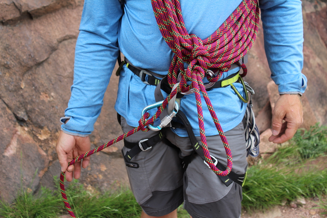 The Kiwi coil for shortening a rope. The rope leading to the next climber is clove- hitched to a carabiner to direct any load to the belay loop.