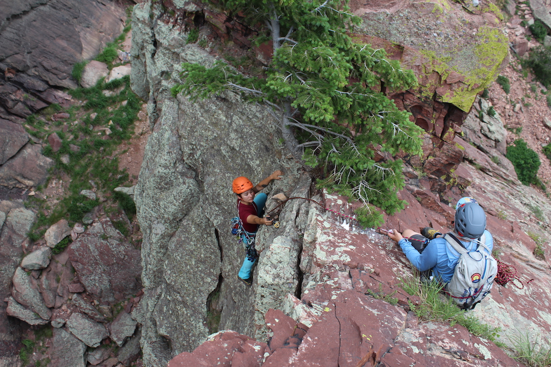 Down-leading a short pitch: The climber places a piece below a tricky step to protect the second person's downclimb. Note the use of friction over a smooth ridge for a terrain belay.