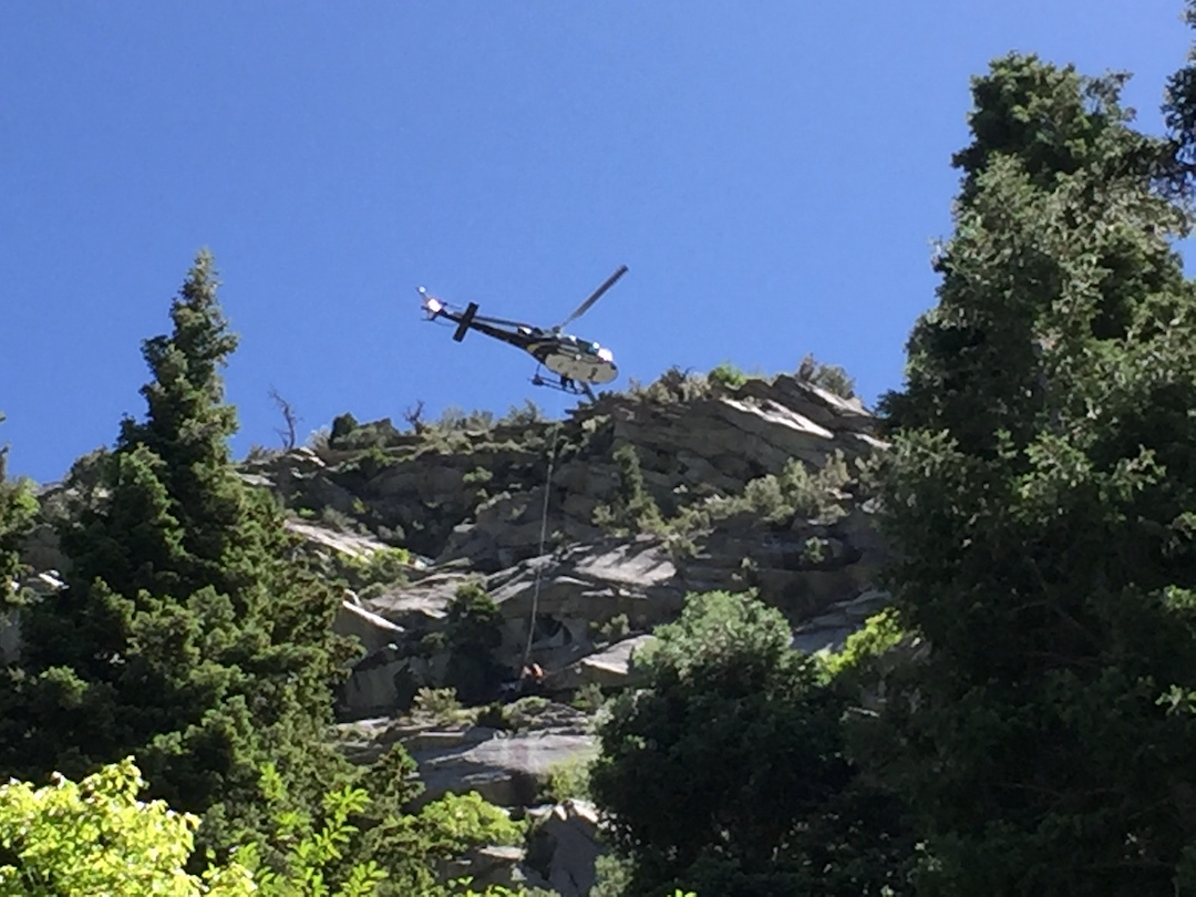 Rescue helicopter prepares to haul off a badly injured climber who fell on the sixth pitch of a route in Little Cottonwood Canyon.